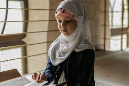 girl in white hijab and blue long sleeve shirt sitting on floor in front of a book